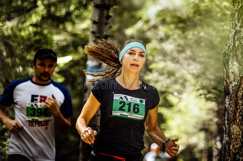 Young active woman athlete runs in forest, loose hair royalty free stock photography