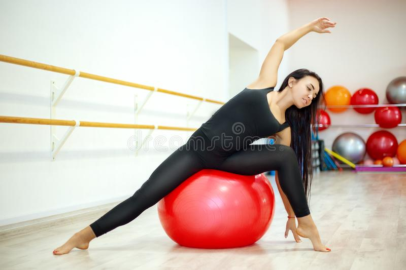 Young active woman in a t-shirt and leggings, performs stretching and yoga exercises in a modern studio. A woman dressed in black sportswear performs exercises royalty free stock photos