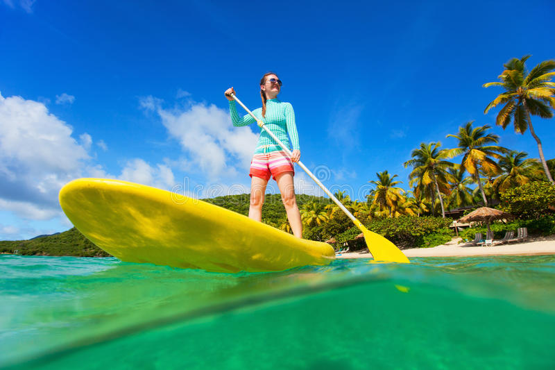 Young active woman on vacation. Split underwater photo of young active woman on tropical beach vacation paddling on stand up board stock photos