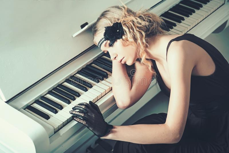Young actress lying on piano overwhelmed with memories. Sad blond girl leaning on keyboard. Roaring twenties fashion royalty free stock photos
