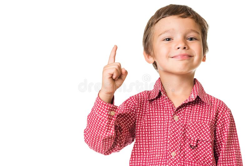 Young boy smiling and pointing finger upwards stock photo