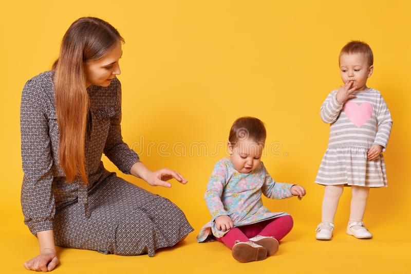Young adorable caring mother looks after her little kids, sitting on floor with one of twin girls. Sweet child puts one hand on stock photo
