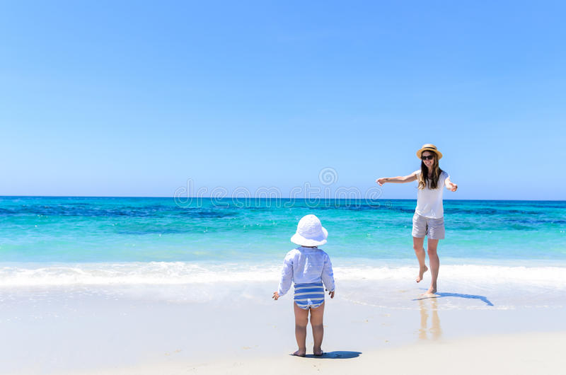 Young adorable mother having fun with little daughter at tropical beach royalty free stock photos