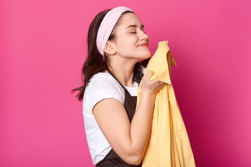 Young adorable woman wears brovn apron and white t shirt, feels satisfied while smells fresh yellow shirt after laundry,  royalty free stock photo