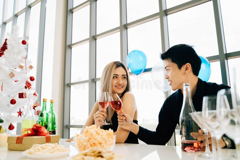 Young adult Asian couple celebrates Christmas party at luxury condo. Young adult Asian couple holding a glass of wine celebrates Christmas party at luxury condo royalty free stock photography