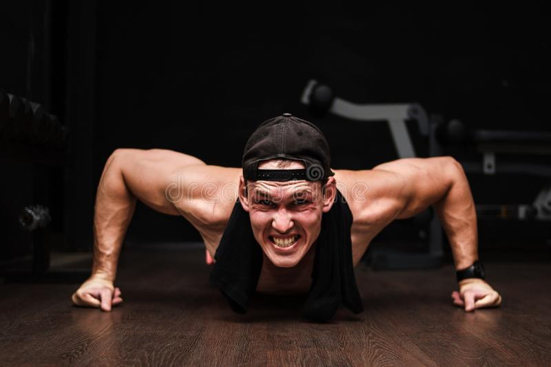 Young Adult Athlete Doing Push Ups As Part Of Bodybuilding Training. Black background stock images