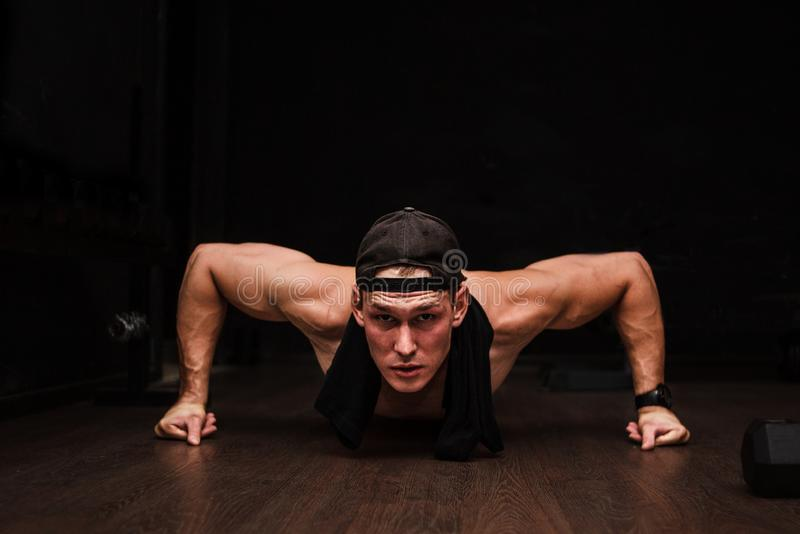 Young Adult Athlete Doing Push Ups As Part Of Bodybuilding Training. Black background royalty free stock photography