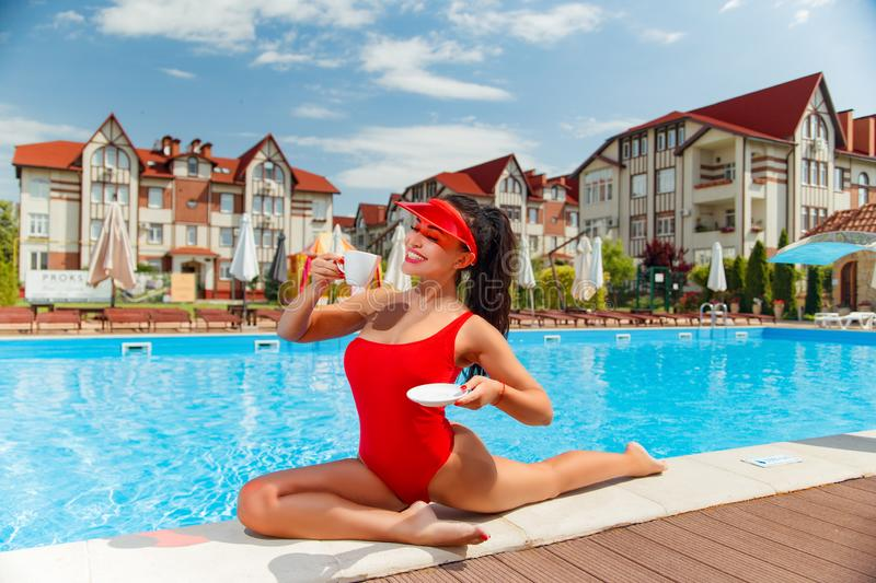 Girl in a red bathing suit near the pool royalty free stock photos