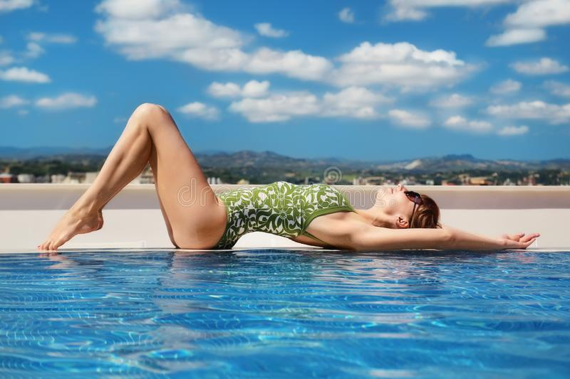 Young adult attractive woman in swimsuite relaxing on rooftop pool edge with blue sky and mountains on background. Beautiful sexy stock photo