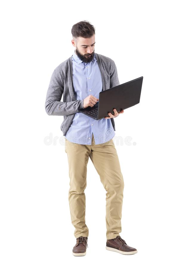 Young adult bearded businessman hold and looks down at laptop computer royalty free stock images