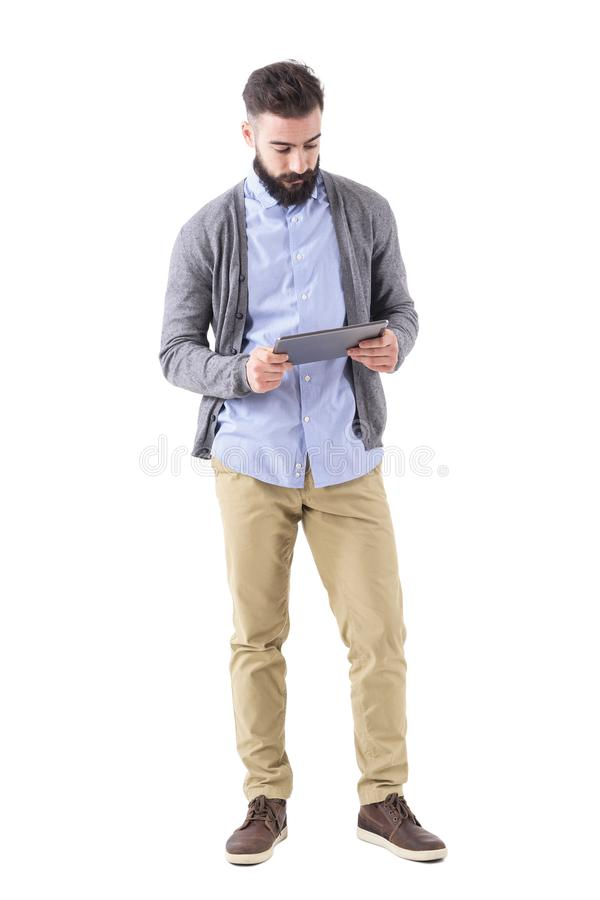 Young adult bearded hipster holding and watching at tablet computer. Full body length portrait isolated on white studio background royalty free stock photography
