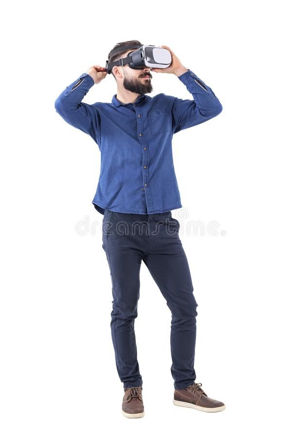 Young adult bearded man trying on virtual reality glasses looking up. royalty free stock photo