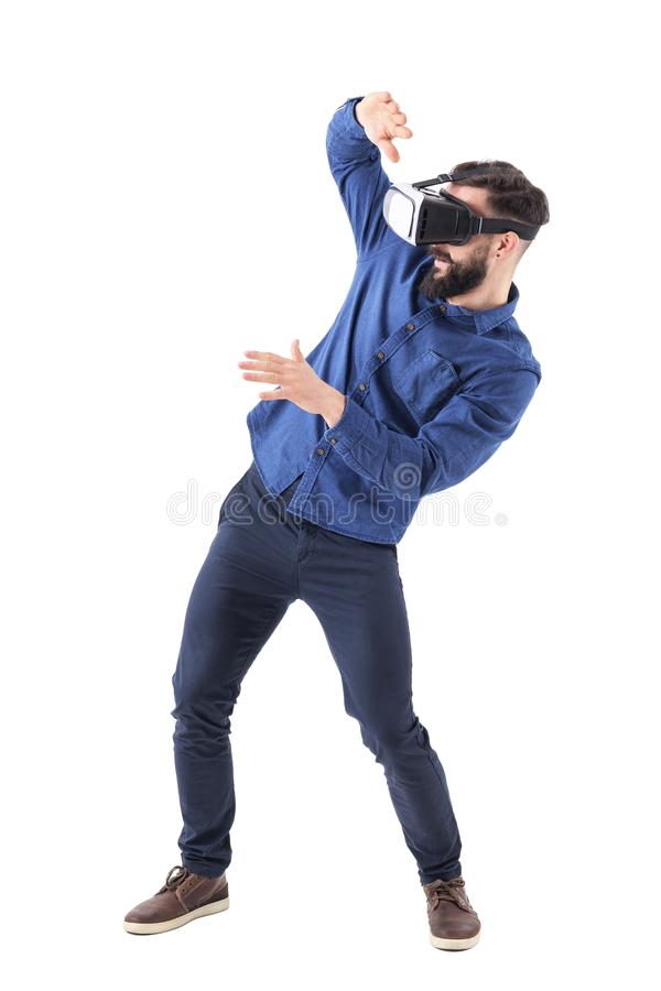 Young adult bearded man with vr glasses bending and shielding with hands playing video game. stock photo