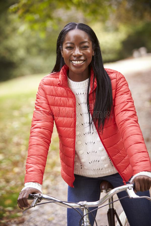 Young adult black woman sitting on a vintage bicycle in a park smiling to camera, front view, close up royalty free stock images