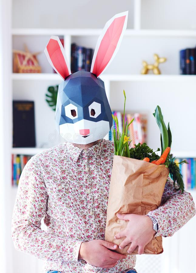 Young adult bunny rabbit holding a paper bag full of fresh greens and carrots stock images