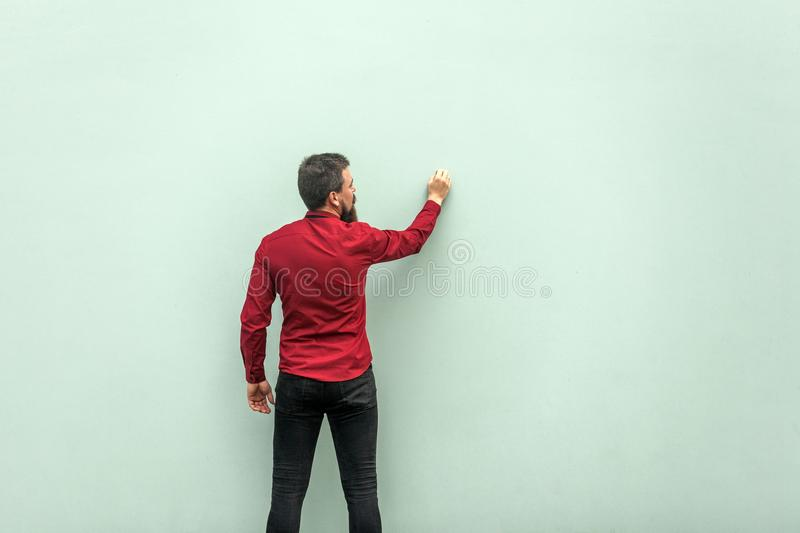 Young adult businessman painting on gray wall stock photos