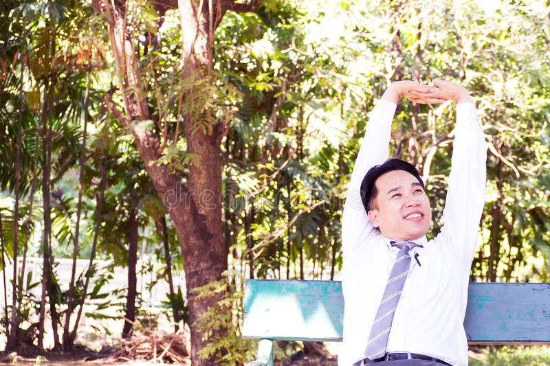 Young adult businessman sitting and relaxing in park. Stretching royalty free stock photography