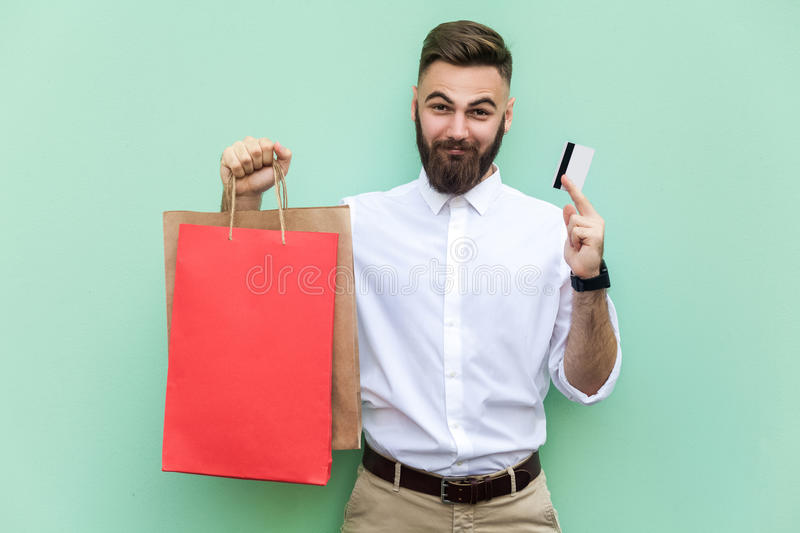 Young adult businessman using credit card for online shopping or banking. Holding credit card on hands and looking at camera. And smile. Indoor, studio shot royalty free stock image