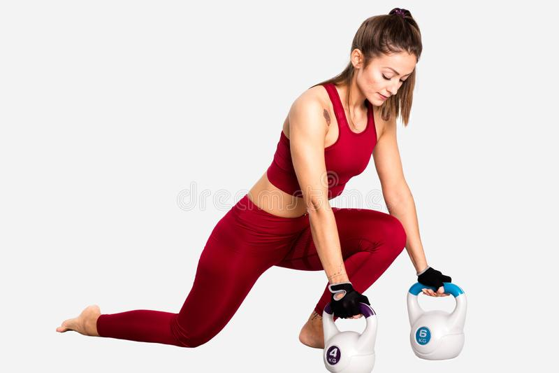 Young adult caucasian girl doing lunge exercise with kettlebell- Image royalty free stock photo