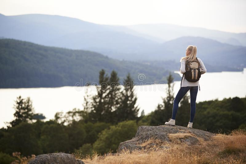 A young adult Caucasian woman standing alone on a peak after hiking, admiring lake view, back view royalty free stock image