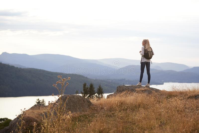 A young adult Caucasian woman standing alone on the rock after hiking, admiring lake view, back view stock images