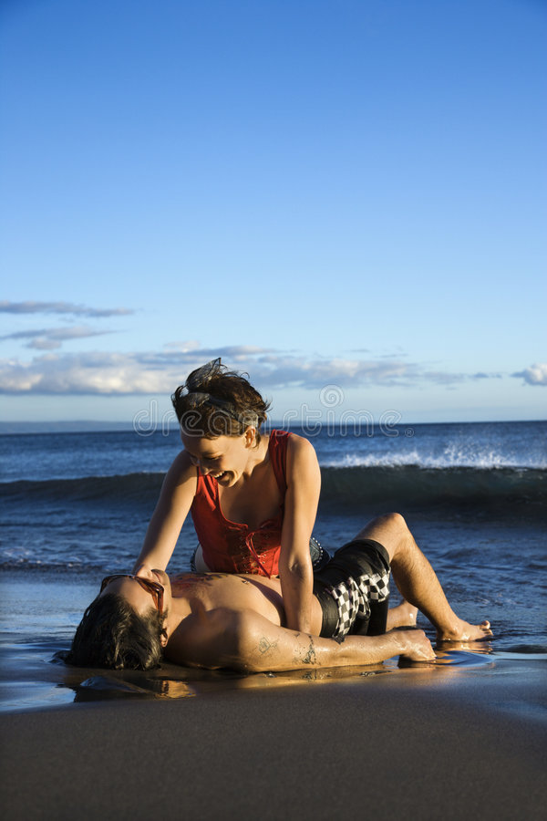 Young adult couple on beach. Caucasian young adult couple frolicking on beach royalty free stock image