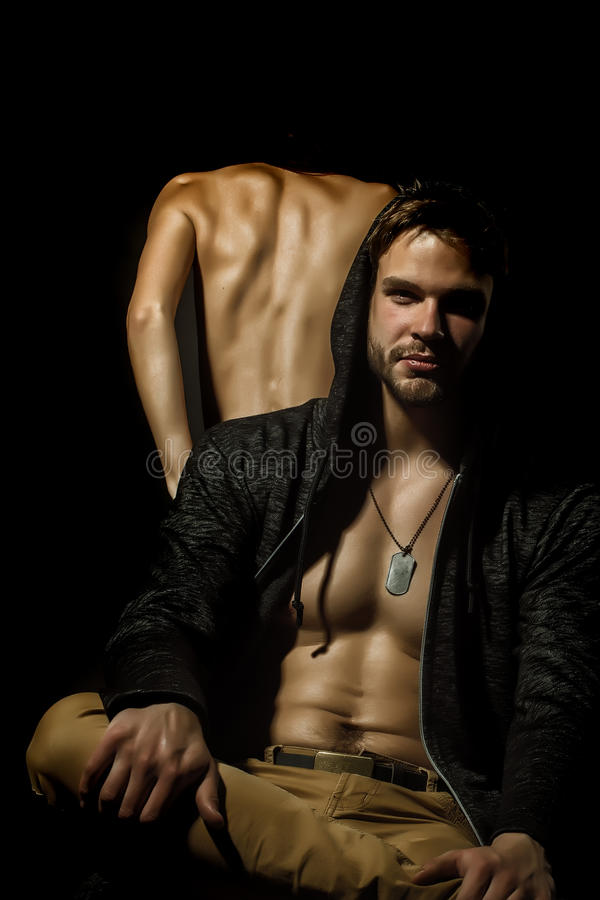 Young adult couple. Young beautiful sexual adult couple of stylish confident men in jacket with hood and naked women with straight body in studio on black stock photography