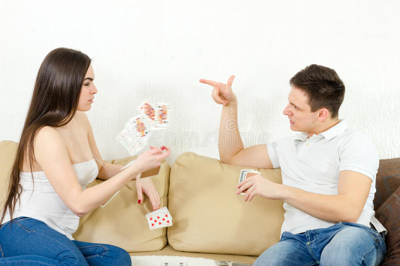 Young adult couple fight over stupid card game. Boyfriend points at his cheating girlfriend and she throws her cards. Angry couple in conflict fighting over royalty free stock images