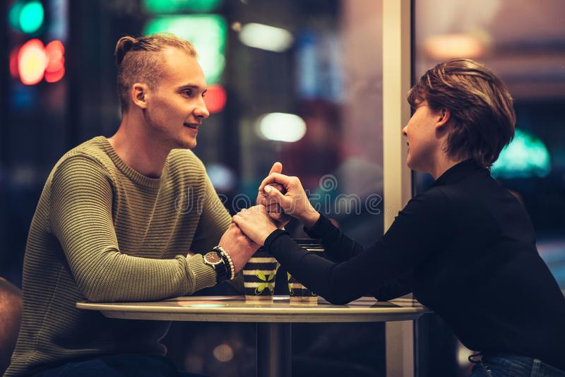 Young adult couple having a date in cafe and drinking coffee holding hands stock photos