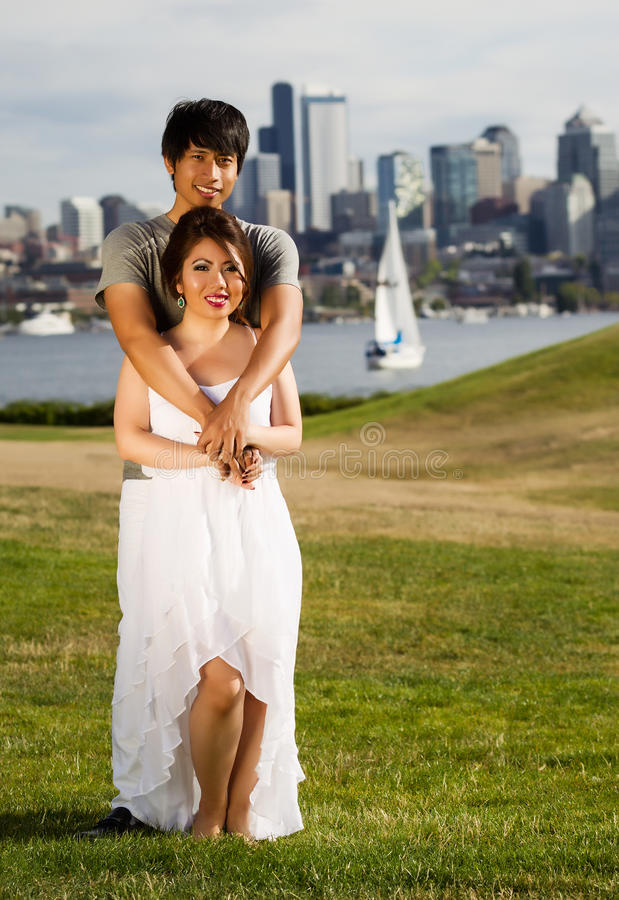 Young Adult Couple Holding each other with City and harbor behin