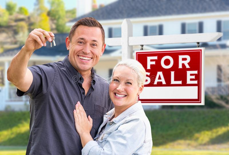 Young Adult Couple With House Keys In Front of Home For Sale Sign. Young Adult Couple With House Keys In Front of Home and For Sale Real Estate Sign stock images