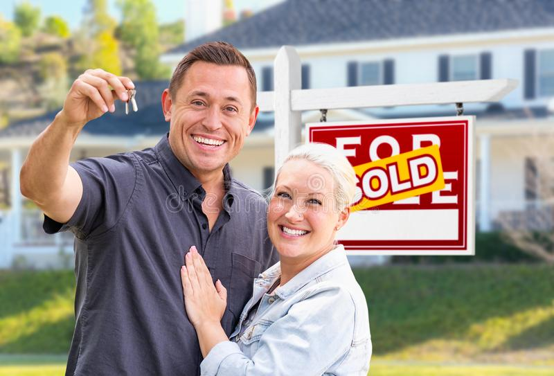 Young Adult Couple With House Keys In Front of Home and Sold Sign. Young Adult Couple With House Keys In Front of Home and Sold For Sale Real Estate Sign stock photos