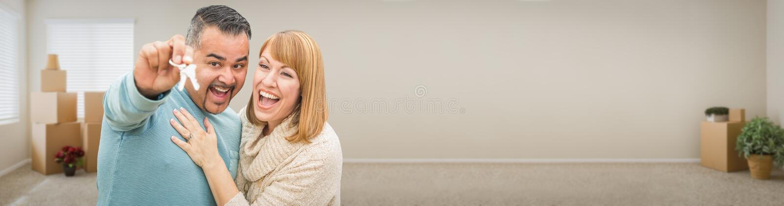 Young Adult Couple Inside Room with Boxes Holding New House Keys. Banner royalty free stock image