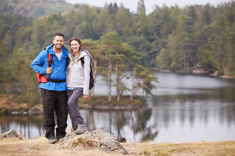Young adult couple standing on a rock beside a lake in countryside, smiling to camera, full length stock images