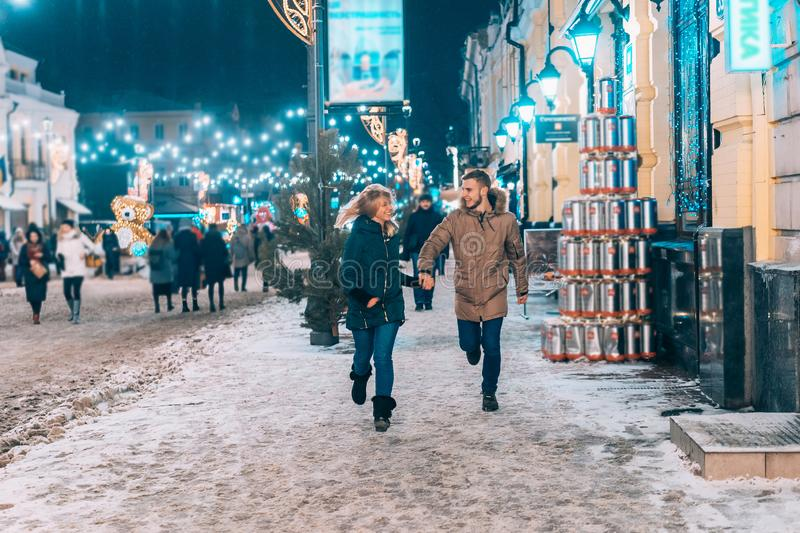 Young adult couple walking on snow covered sidewalk. Young adult couple holding each other hands and walking on snow covered sidewalk stock photography
