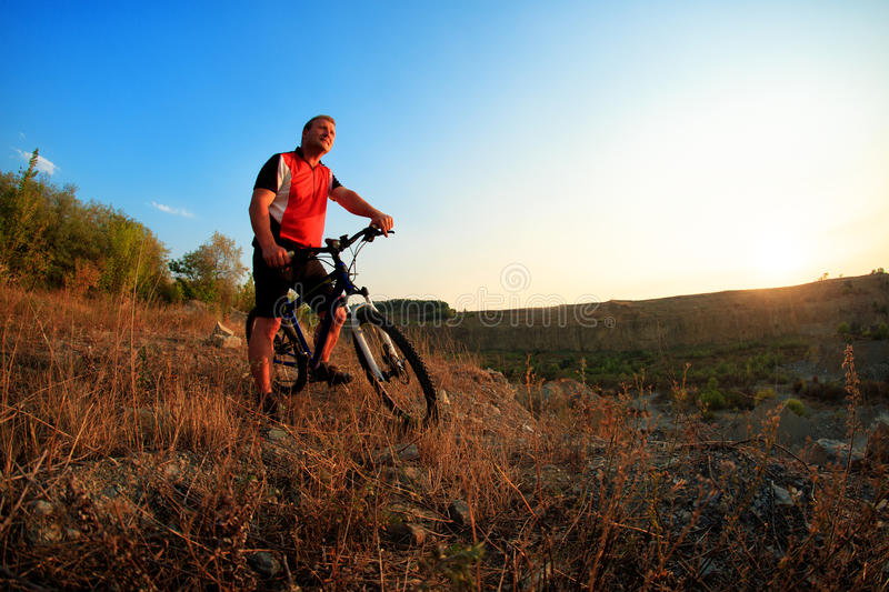 Young adult cyclist riding mountain bike in the countryside royalty free stock photography