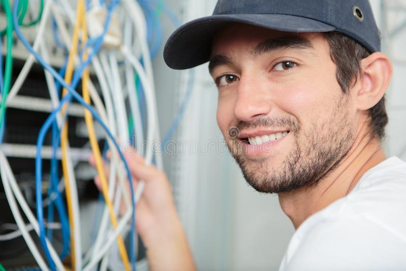 Young adult electrician in front fuse switch board royalty free stock photography