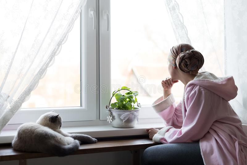 Young adult female cancer patient wearing headscarf and bathrobe sitting in the kitchen with her pet cat. royalty free stock image