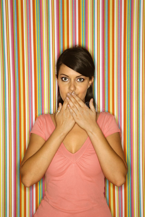 Young adult female Caucasian covering mouth. Young adult female Caucasian covering mouth on striped background royalty free stock image
