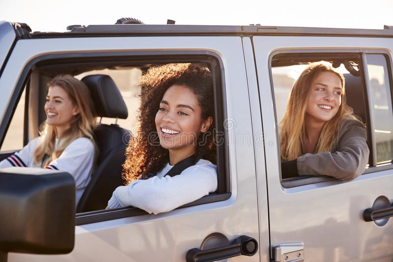 Young adult female friends going on vacation in a car stock photos