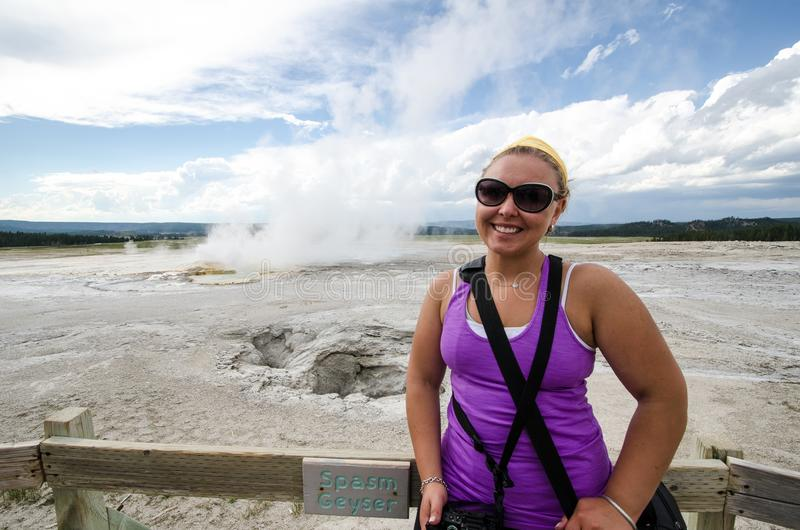 Young adult female tourist stands near Spasm Geyser in Yellowstone National Park stock photography