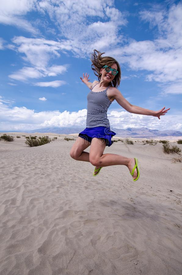 Young adult female woman jumps in the Mesquite Sand Dunes in Death Valley National Park in California stock photos