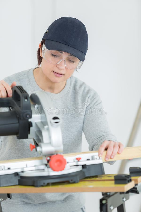 Young adult female woodworker cutting board in workshop royalty free stock images