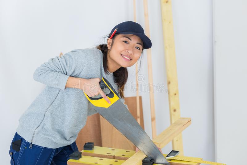 Young adult female woodworker hand sawing in workshop royalty free stock image