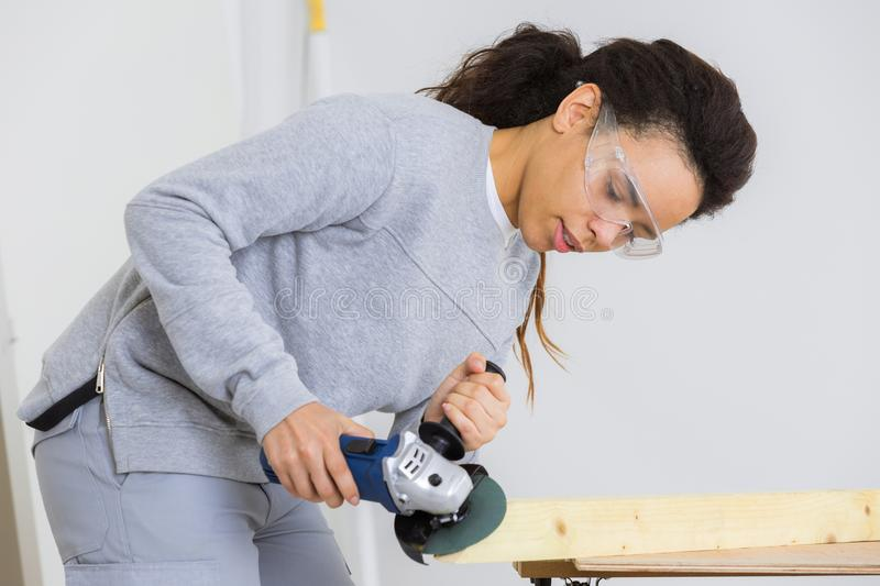 Young adult female worker grinding plank with electric grinder royalty free stock image