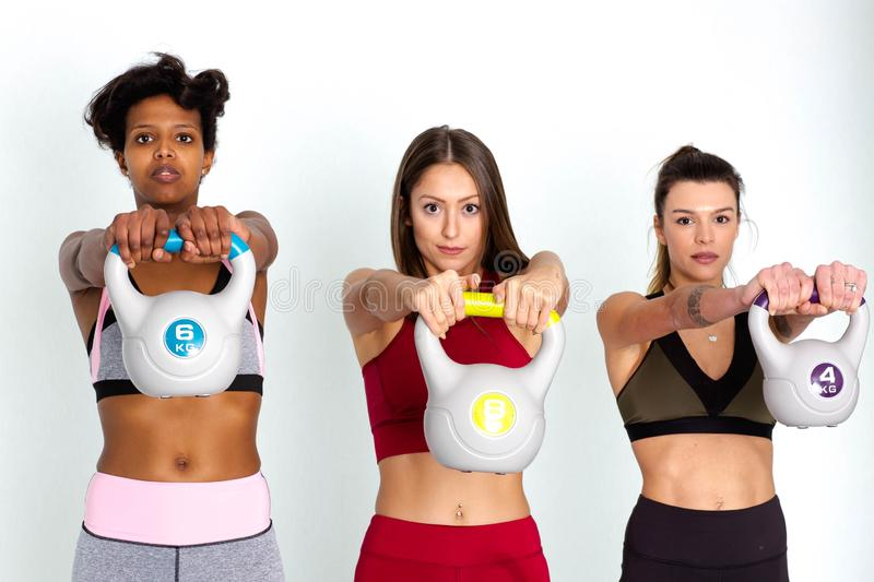 Young adult fitness women doing swing exercise with a kettlebell. Group of female athletes lifting kettlebells - Image royalty free stock photos
