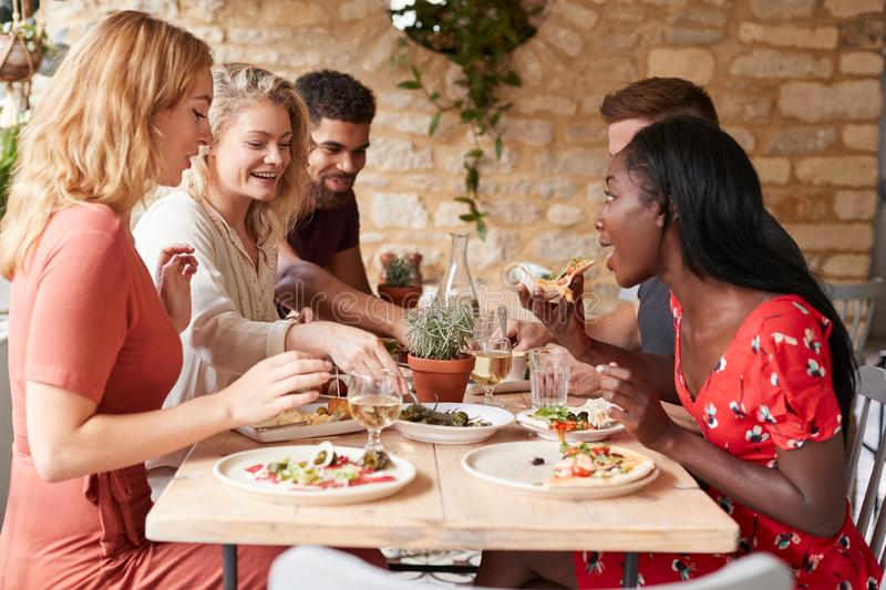 Young adult friends eating lunch at a table in a restaurant stock photo