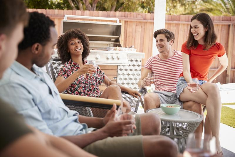 Young adult friends relaxing on the porch outside a house stock image