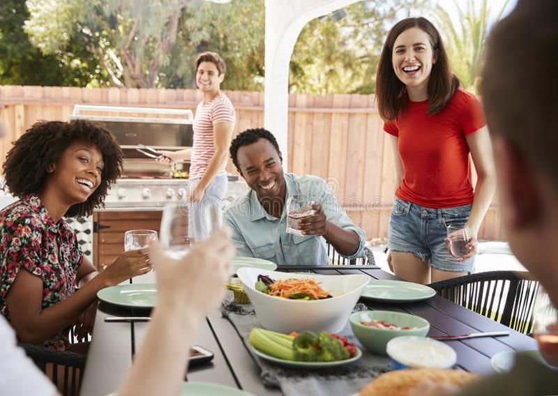 Young adult friends sitting outdoors for lunchtime barbecue stock images