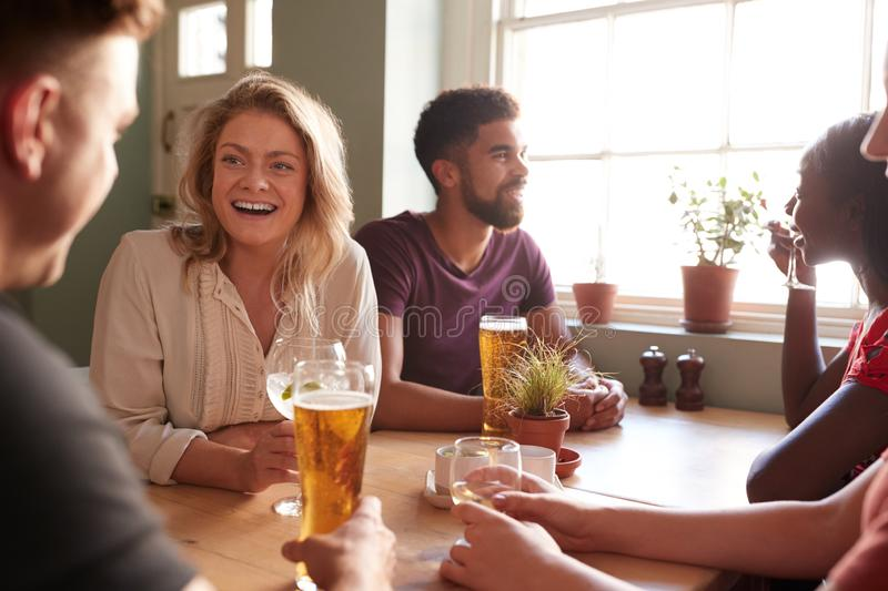 Young adult friends talking at a table in a pub royalty free stock photography